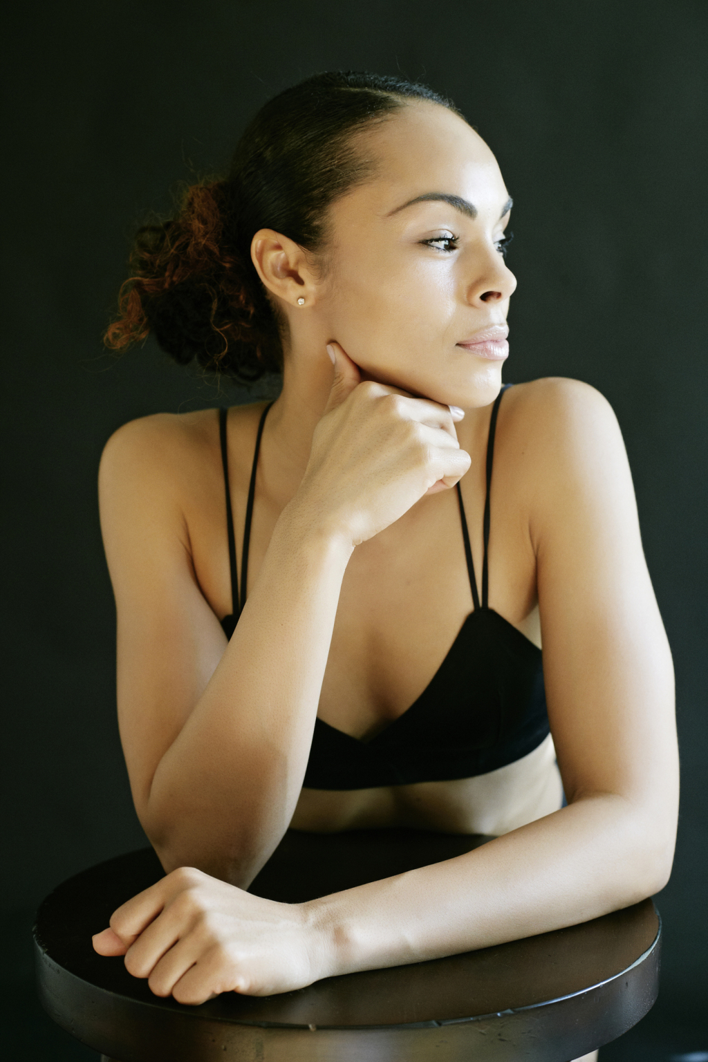 Pensive Mixed Race woman wearing bra leaning on stool